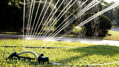 stock-footage-a-lawn-sprinkler-wasting-water-by-not-only-watering-a-parched-lawn-but-the-driveway-as-well